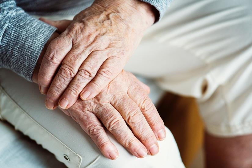 Close up of elderly person's hands, crossed over their knee.