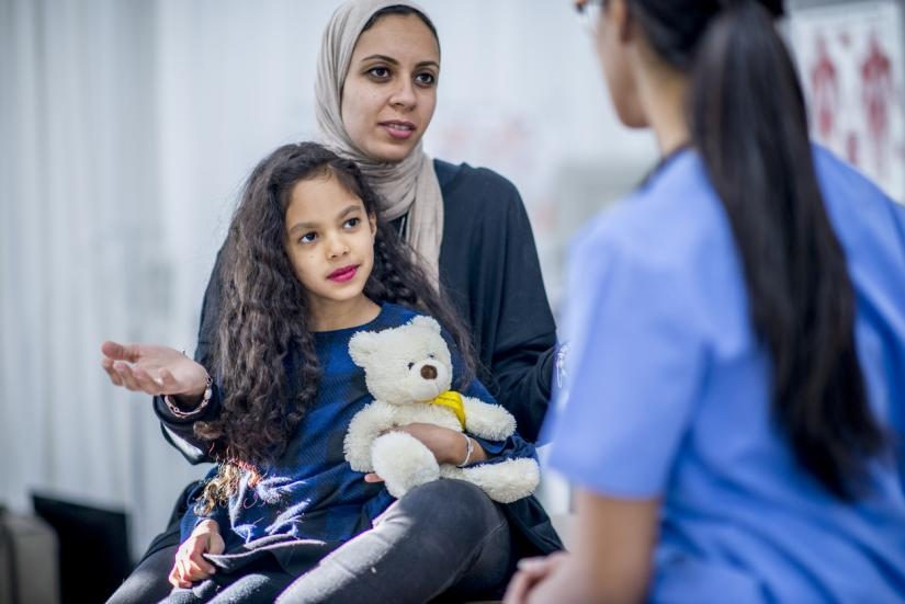 A refugee woman and her child in consultation with a doctor