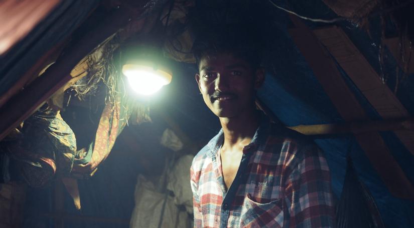 An Indian man smiling next to a solar light