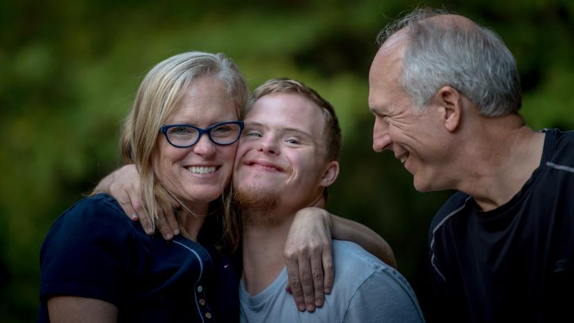Photo of parents with their Down Syndrome son, by Nathan Anderson on Unsplash