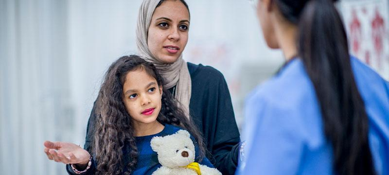 Refugee child and mother speaking to doctor