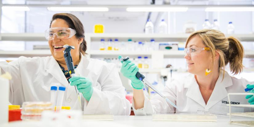 two researchers in a lab laughing
