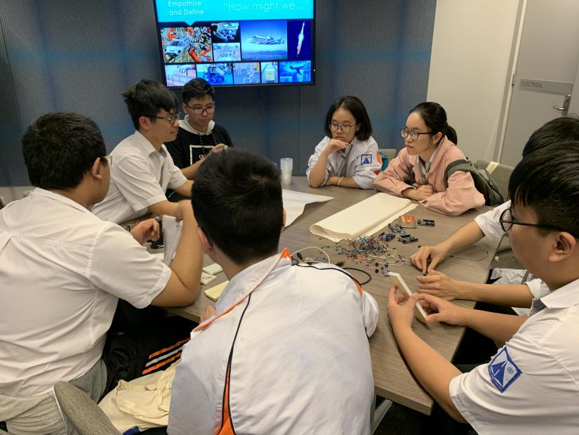 A group of students sit around a table and examine circuitry