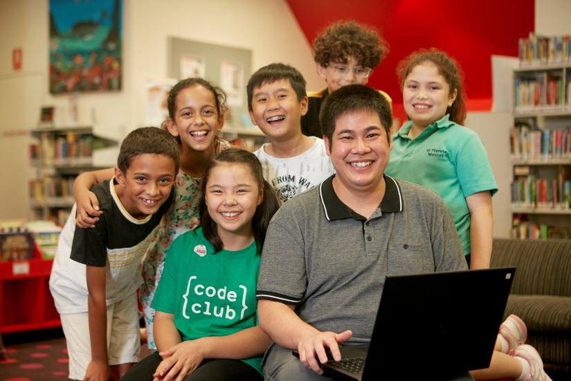 Chau Au posing with students from his Code Club program.