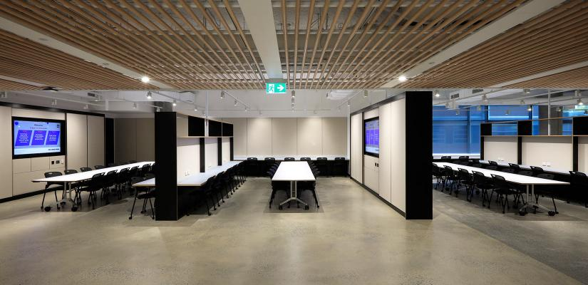 Collaborative pods with long work tables, cabinetry and AV