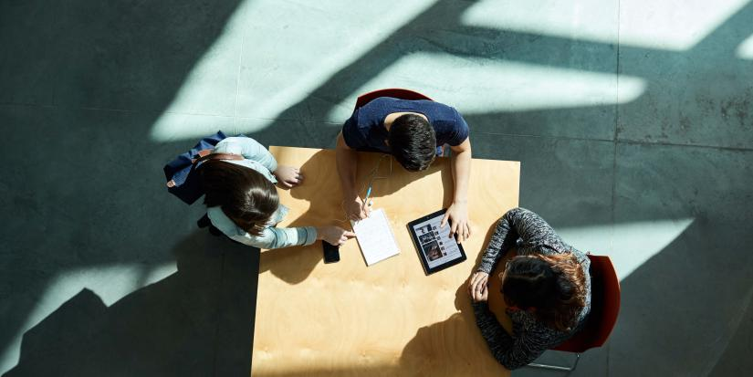 Overhead photo of three students sitting at a table with a notepad and an iPad
