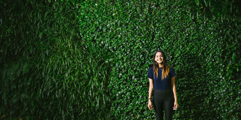 young female student standing in front of green wall at UTS