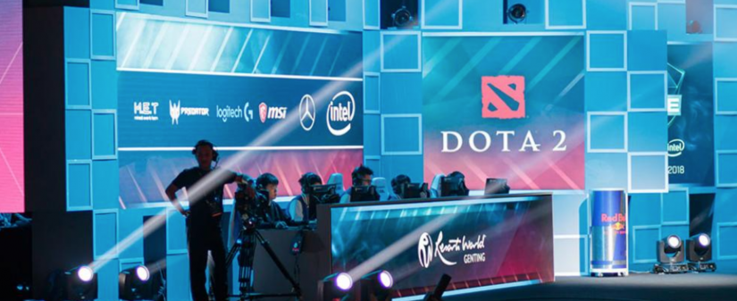 An Esports team playing on computers on a stage, in front of a Dota 2 banner.