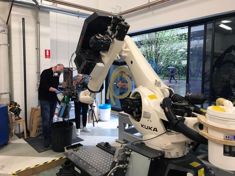 Staff use a large robot arm to 3D print EPS