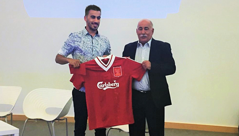 Hakeem Al-Araibi receives a jersey signed by Liverpool legend Robbie Fowler from Rabieh Krayem, chairman of the Association of Australian Football Clubs.