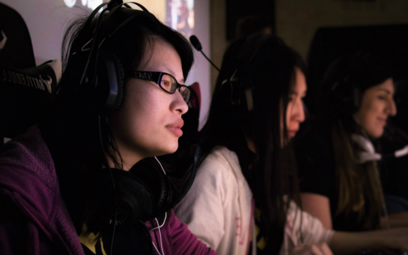 Women looking focussed, sitting at computers with gaming headsets on