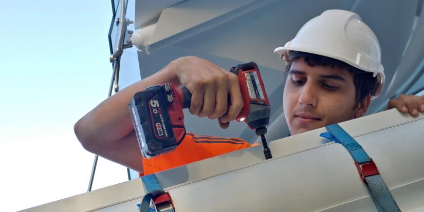 UTS student Simon Thorby wearing a hard hat and using a drill to help construct a piece of sun shading
