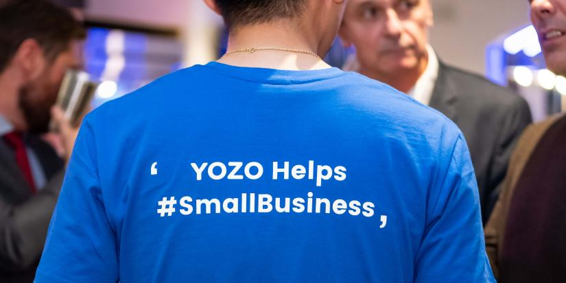 "Closeup of the back of a person in a blue t-shirt with white writing ""YOZO helps #SmallBusiness"""