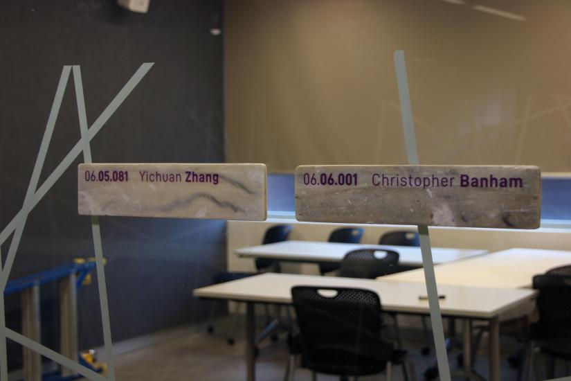 Two office signs made of EPS attached to a glass wall