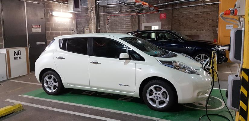 A white hatchback EV uses the charge point, which is a car space painted green with wall-mounted AC chargers that connect to the car with heavy duty cables