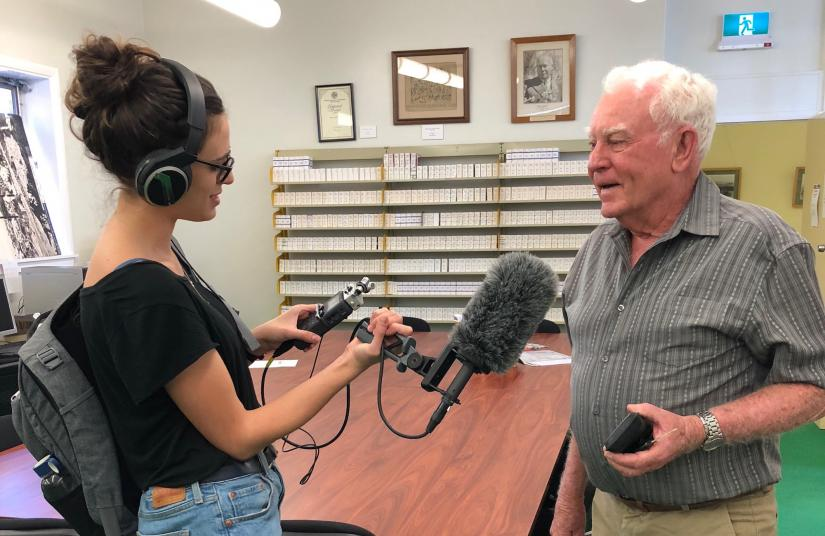 A young female reporter records an interview with an elderly man