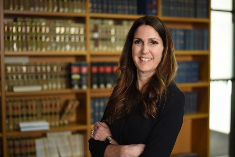 Lawyer Jo Pugsley smiling in front of a bookcase with her arms crossed. She is wearing a long sleeve black top and has long brown hair.