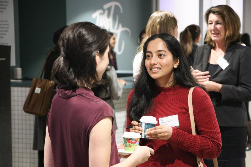 Female student speaking with female professional at networking event