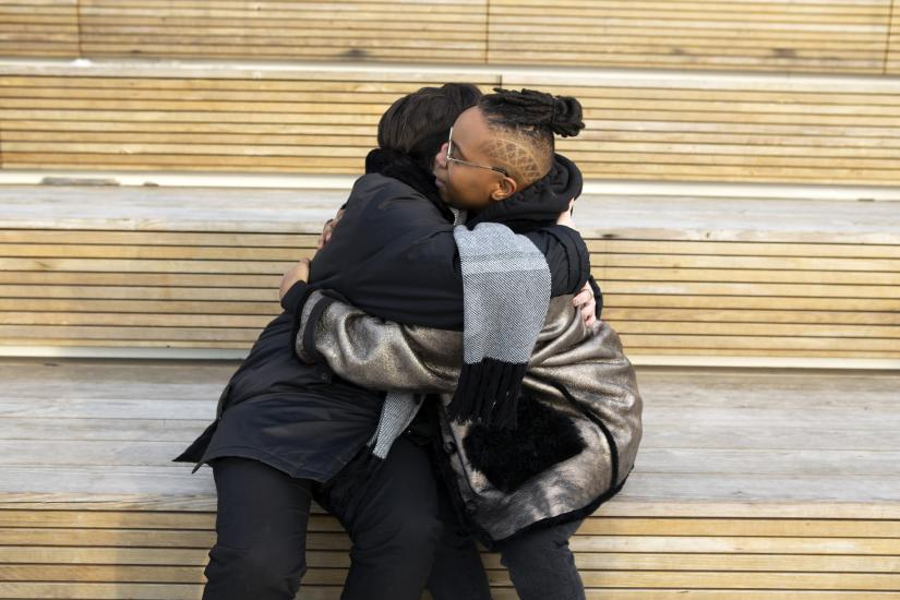 Two people hugging on a bench