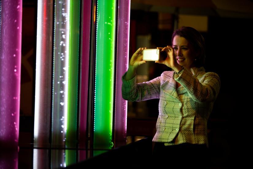 Woman takes photo of Vivid algae lights at festival in Sydney.