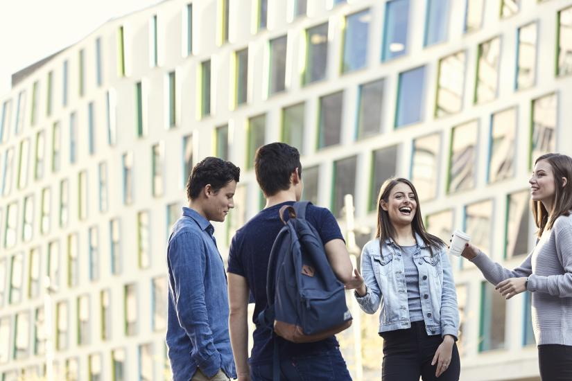 Four students standing and laughing. Behind them are the Building 7 windows