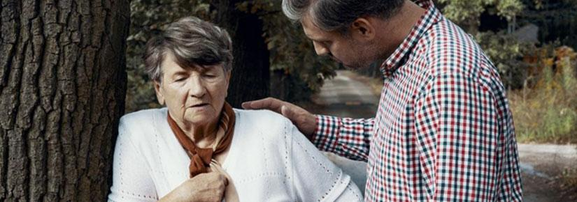 Man with caring hand on shoulder of elderly woman