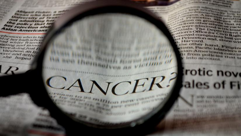 Magnifying glass focusing on the word 'cancer' in a newspaper. Image by PDPics from Pixabay
