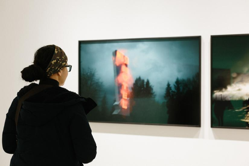 Student viewing photographic pieces on a gallery wall