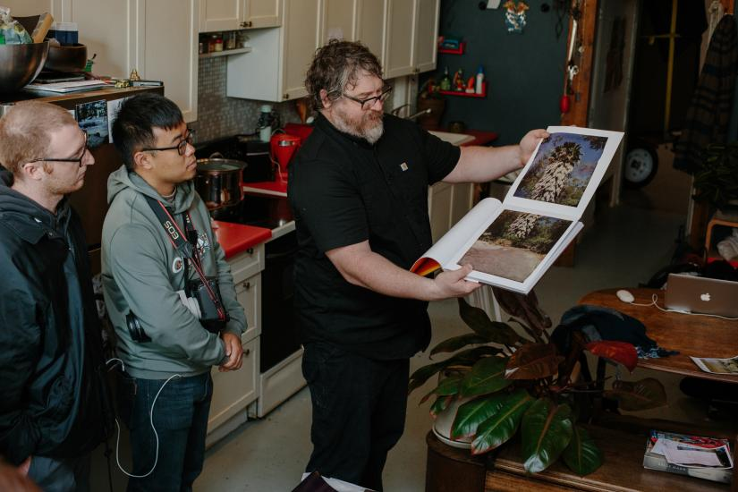 Photographic artist John Chiara shows two UTS students photographs from a book.