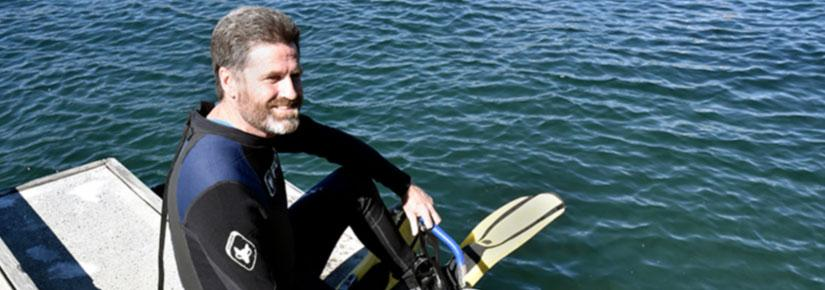 David Booth on edge of boat in diving gear smiling