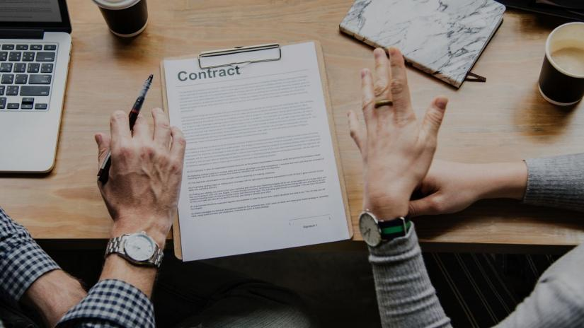A contract is sitting on a table, and two hands are hovering over it