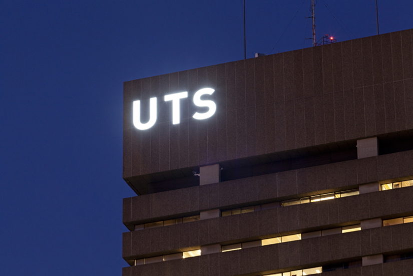 Top corner of UTS tower with illuminated letters by night