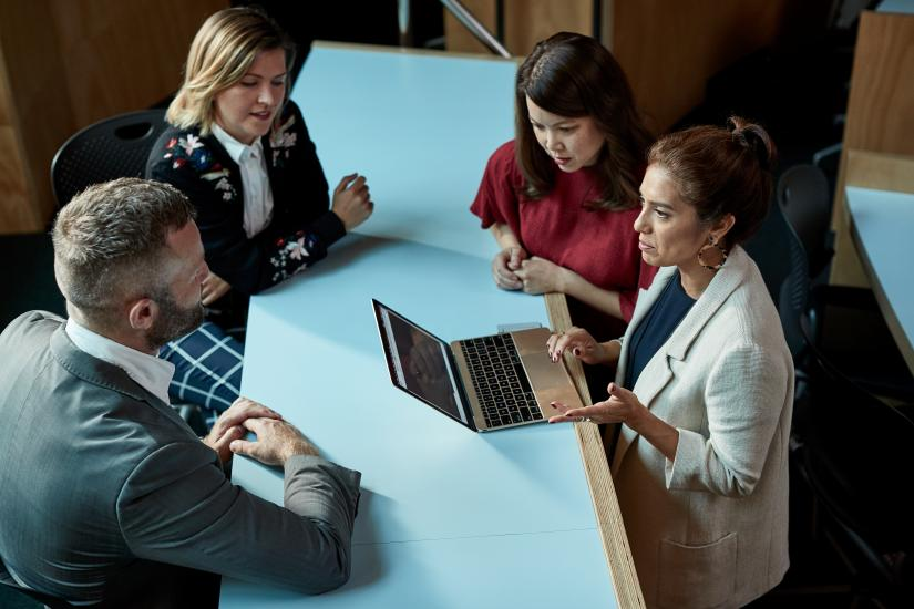 A women with laptop in discussion with one male and two female colleagues around a work table.