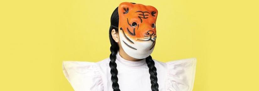 A person with dark plaits in a white dress wearing a plastic tiger mask. The background is solid yellow