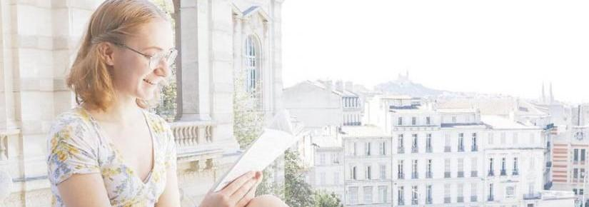 Emily Mead sitting on a balcony with a book in France