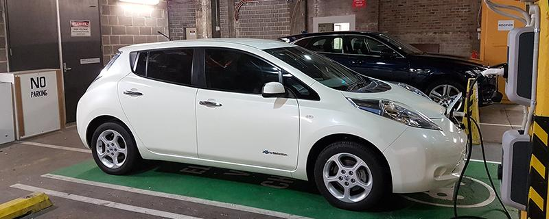 A white electric car charges at the Building 10 EV charge point.