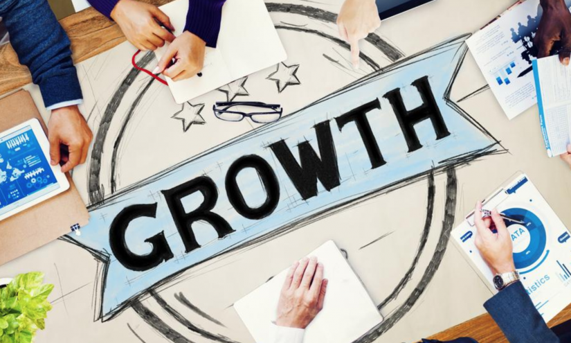 Bird's eye view of a table at a meeting. A large piece of paper has the word 'GROWTH' written on it.
