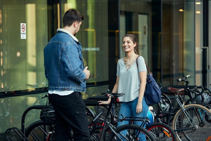 Two people standing next two bikes smiling at each other
