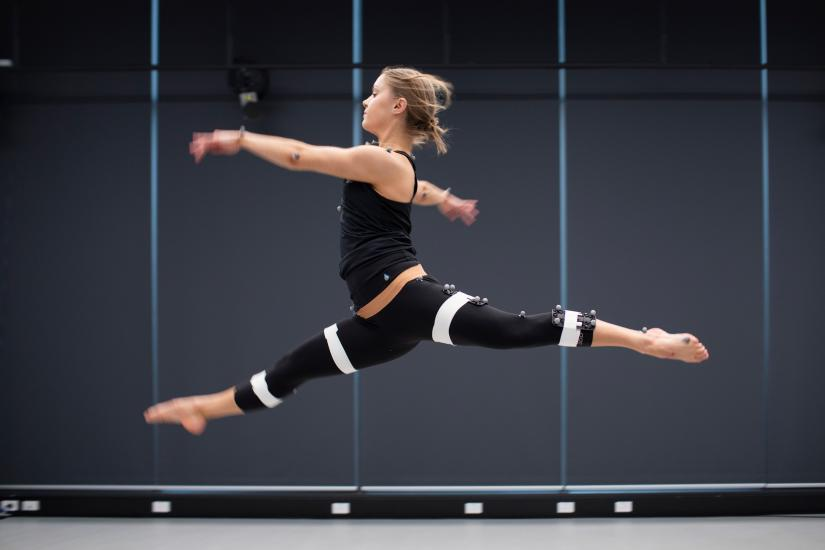 Woman jumping with motion sensors attached to her body