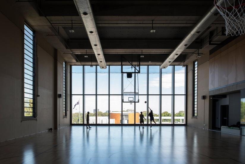 A hall with 3 people playing basketball