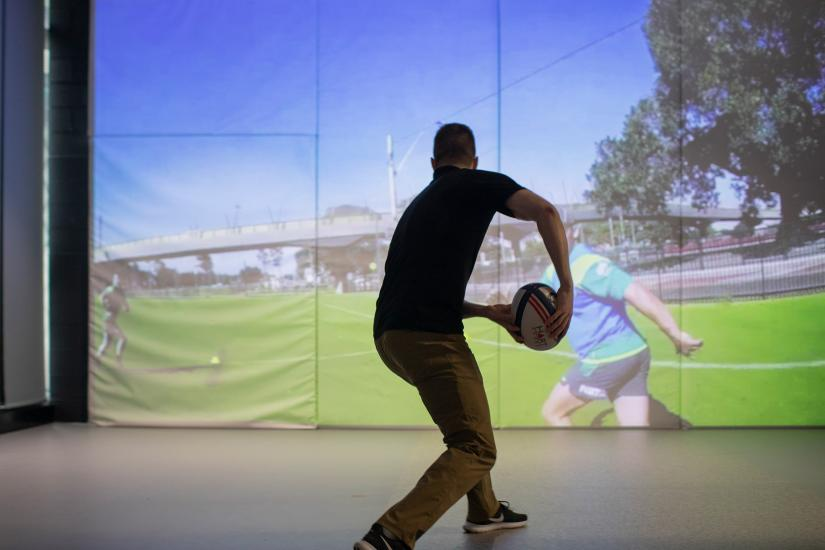 Man about to pass a football in front of a projection screen