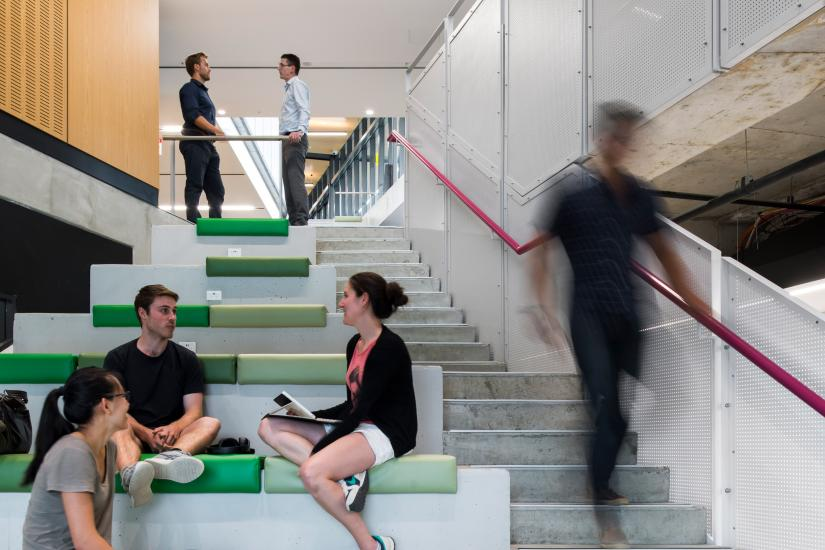3 people sit on seats along a stairway