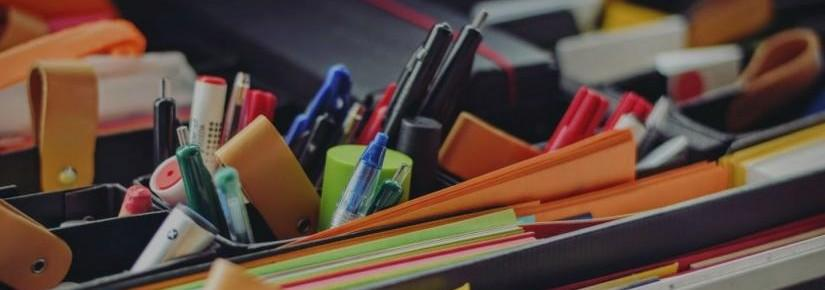 Close up image of stationary, including pens, paper and highlighters