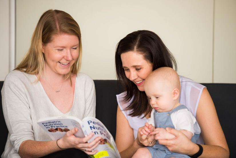 A child and family health nurse works with a mother and infant