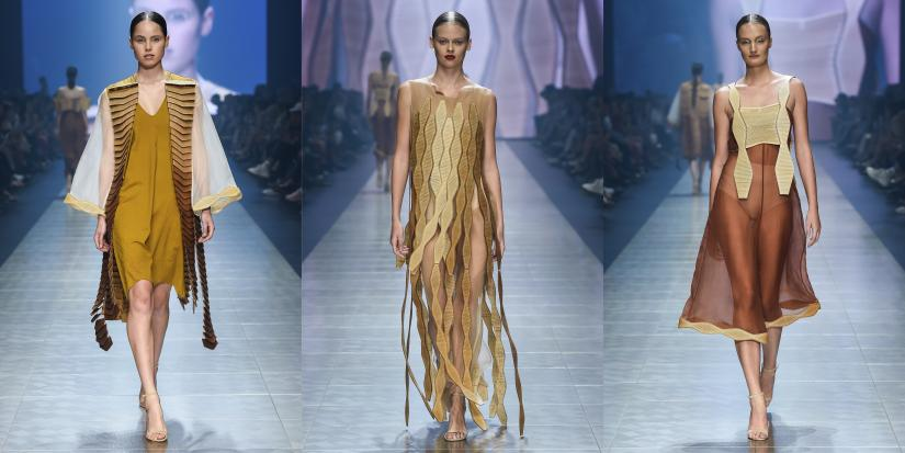 Three images side-by-side of a brightly-lit fashion runway, with a seated crowd on either side. In each image, a model wears one of Jessica's designs. The cuts in the wood allow the pieces to flow as the models walk.