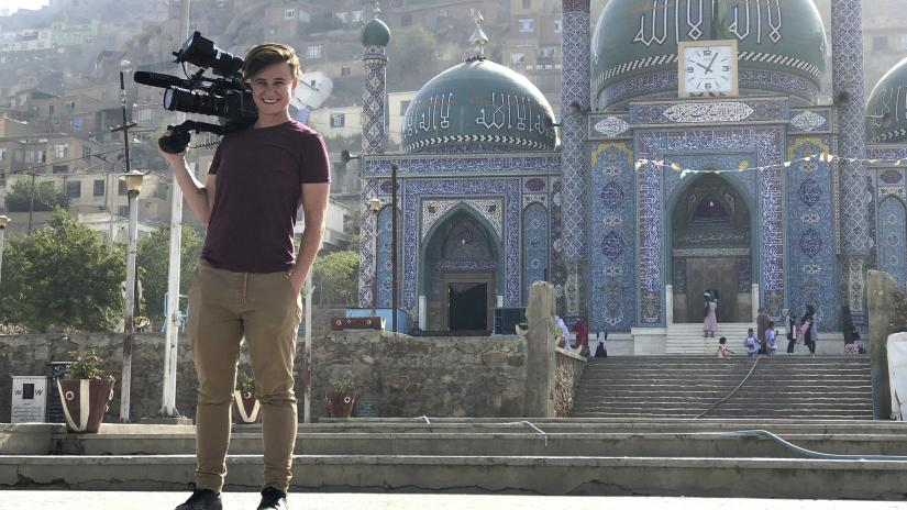 Jordan Bryon stands smiling, with a film camera resting on their shoulder. Behind them is an intricately decorated mosque and a dusty hill-side city.