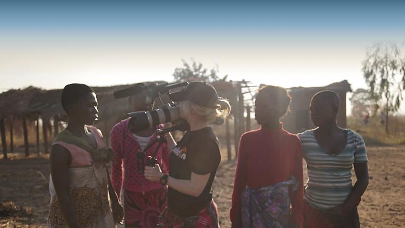Christel Cornilsen, a blonde woman wearing a baseball cap, stands holding a film camera in a dusty rural landscape in Malawi. She is in conversation with four Malawian women.