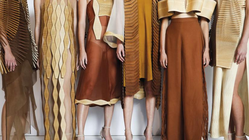 Close-up of fashion outfits worn by six models. The clothes are made from silk and wool in warm brown and cream tones. All include edgings or overlays made of laser-cut wood.