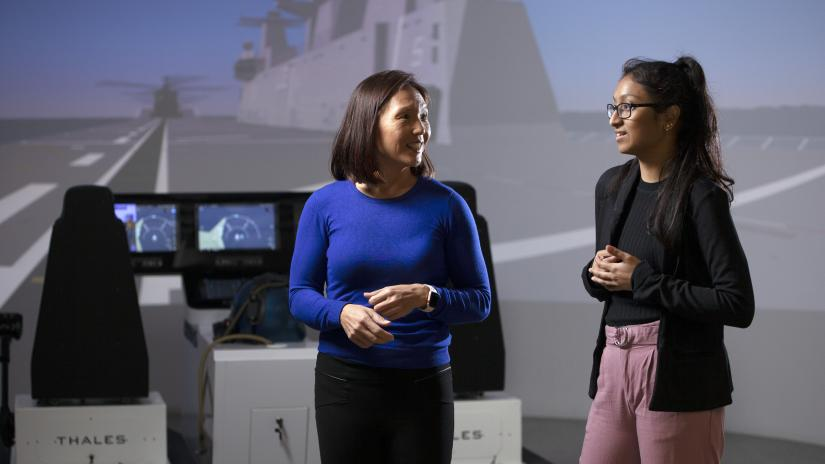 Two women, Eva Wong and Manjusha Pinni, stand in conversation. Behind them is a flight simulator, including two chairs with controls and radar screens, and a full screen projection of an aircraft runway.