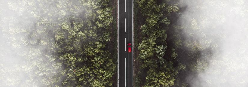 Aerial photo of a forest. A road runs through the centre, with a red car driving along it.